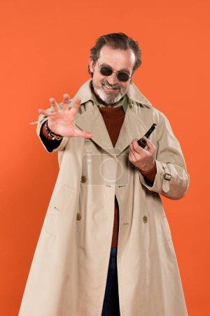 Photo pour Mode homme senior tenant pipe de tabagisme en se tenant debout, isolé sur orange - image libre de droit