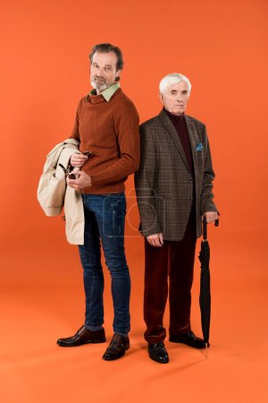 Photo for Trendy retired man standing with jacket in hands near friend with umbrella on orange background - Royalty Free Image