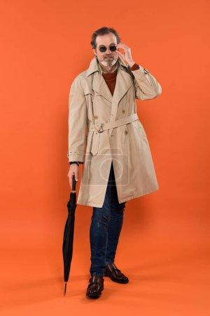 Photo pour Mode homme senior touchant les lunettes de soleil et tenir le parapluie sur fond orange - image libre de droit
