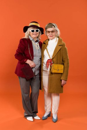 Photo for Stylish retired women standing and smiling on orange background - Royalty Free Image