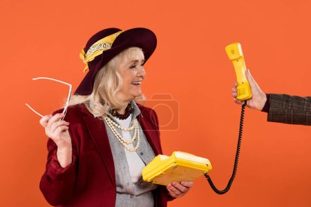 cropped view of retired man holding retro phone in hand near cheerful senior woman isolated on orange