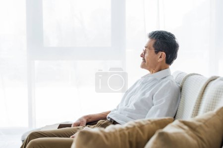 Photo for Thoughtful senior man sitting on sofa at home - Royalty Free Image