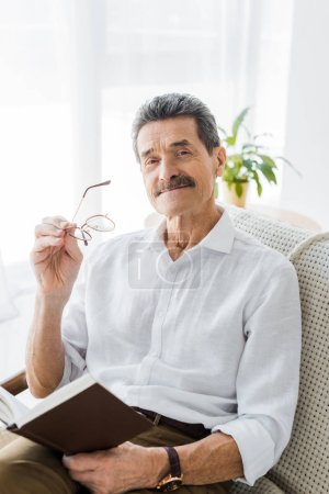 Photo for Cheerful senior man holding book and glasses at home - Royalty Free Image