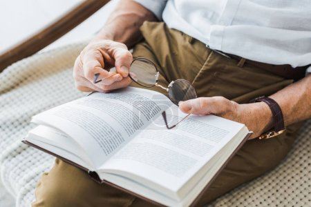 Photo for Cropped view of senior man reading book and holding glasses at home - Royalty Free Image