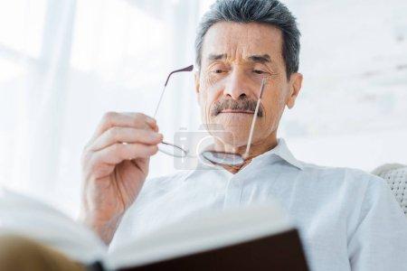 Foto de Senior hombre leer libro y usar gafas en casa - Imagen libre de derechos
