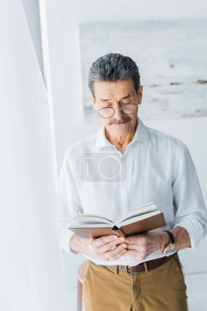 Photo for Senior man in glasses standing and reading book at home - Royalty Free Image