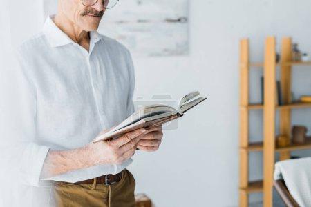 Foto de Vista recortada de senior hombre permanente y lectura en el hogar - Imagen libre de derechos