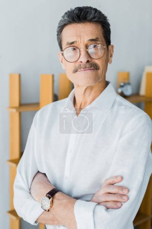 Photo for Retired man in glasses standing with crossed arms at home - Royalty Free Image