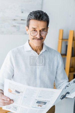 Photo for Happy senior man in glasses holding newspaper at home - Royalty Free Image