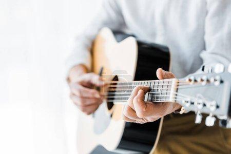 Photo pour Recadrée de l'homme senior, jouer de la guitare acoustique à la maison - image libre de droit