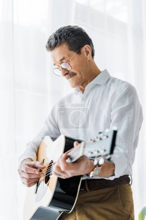 Photo for Retired man in glasses playing acoustic guitar at home - Royalty Free Image