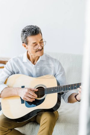 Photo for Cheerful senior man in glasses playing acoustic guitar at home - Royalty Free Image