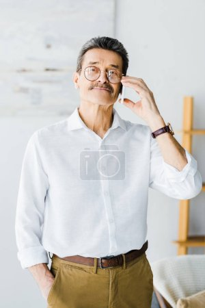 Photo for Cheerful senior man talking on smartphone at home - Royalty Free Image