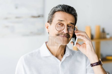 Photo for Cheerful senior man in glasses talking on smartphone at home - Royalty Free Image