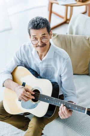 Photo for Cheerful pensioner in glasses playing acoustic guitar at home - Royalty Free Image