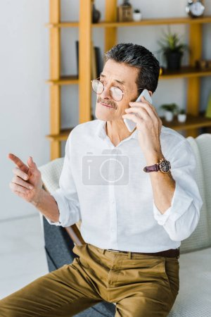Photo for Retired man in glasses talking on smartphone at home - Royalty Free Image