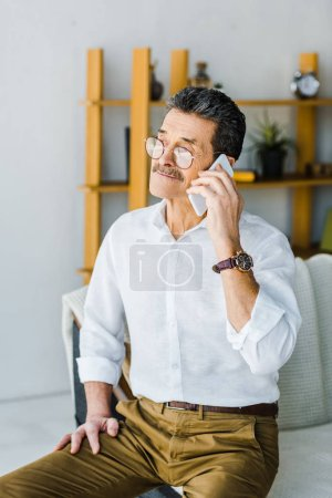 Foto de Pensionista en gafas hablando en teléfono inteligente en el hogar - Imagen libre de derechos