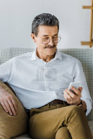 Photo for Happy senior man in glasses looking at smartphone at home - Royalty Free Image