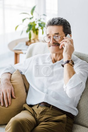 Photo for Happy senior man with mustache talking on smartphone at home - Royalty Free Image