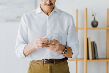 Photo for Cropped view of senior man using smartphone at home - Royalty Free Image
