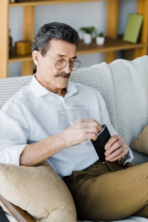 Photo for Senior man in glasses looking at alcohol flask at home - Royalty Free Image
