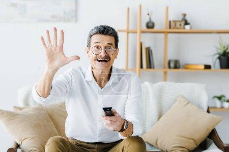 Photo pour Homme âgé joyeux assis sur le canapé et tenant la télécommande tout en agitant la main - image libre de droit
