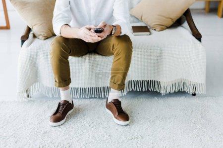 Photo pour Vue recadrée de l'homme âgé assis sur le canapé et tenant la télécommande - image libre de droit