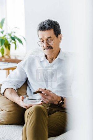 Photo pour Senior homme tenant sigar et cendrier dans les mains - image libre de droit