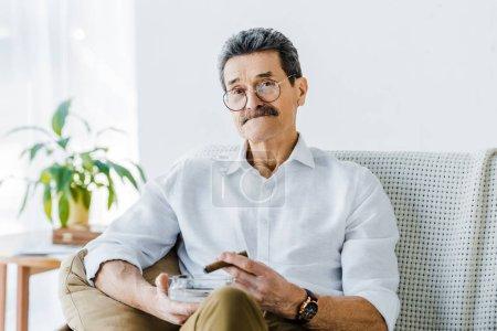 Photo pour Senior homme avec moustache tenant sigar et cendrier en mains - image libre de droit