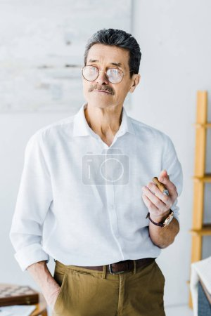 Photo for Senior man holding sigar and standing with hand in pocket - Royalty Free Image
