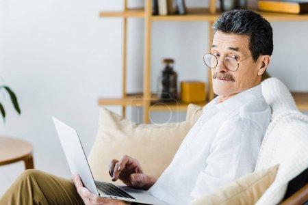 Foto de Hombre senior sorprendido usando laptop sentado en el sofá - Imagen libre de derechos