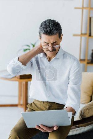 Foto de Pensativo pensionista con bigote mirando portátil en casa - Imagen libre de derechos