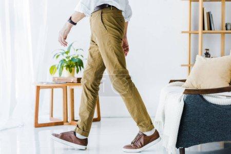 Photo pour Recadrée vue senior homme marchant à la maison moderne - image libre de droit
