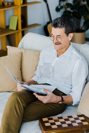 Photo for Cheerful pensioner in glasses reading newspaper while sitting on sofa - Royalty Free Image