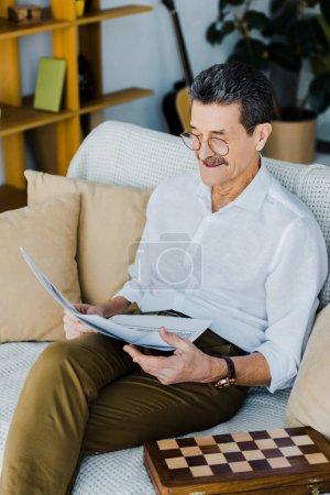 Photo pour Joyeuses retraités dans des verres en lisant le journal tout en étant assis sur le canapé - image libre de droit