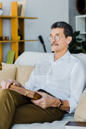 Photo for Pensioner in glasses holding chess board while sitting on sofa - Royalty Free Image