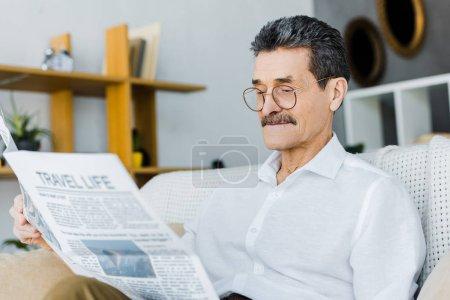 Photo pour Homme âgé joyeux dans des lunettes lecture journal de voyage tout en étant assis sur le canapé - image libre de droit