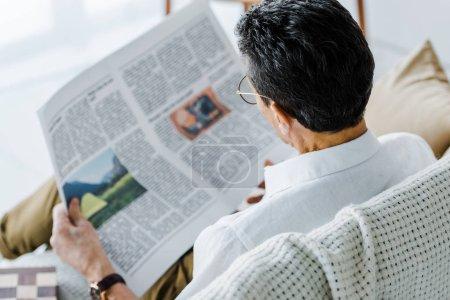 Foto de Enfoque selectivo del hombre leyendo periódico en casa - Imagen libre de derechos