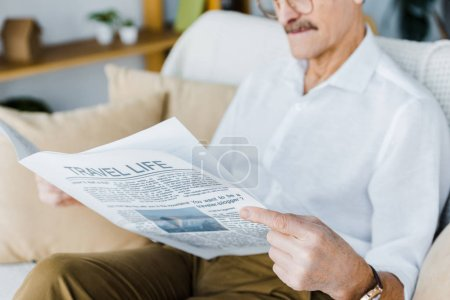 Photo for Cropped view of senior man reading travel newspaper while sitting on sofa - Royalty Free Image