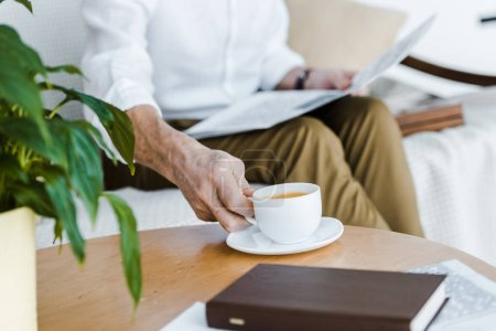 Photo for Cropped view of retired man holding cup with coffee and newspaper at home - Royalty Free Image