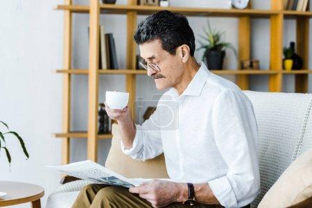 Foto de Hombre jubilado en gafas sosteniendo la taza con café y leyendo el periódico en casa - Imagen libre de derechos