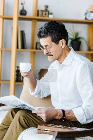 Foto de Pensionista en gafas sosteniendo la taza con café y leyendo el periódico en casa - Imagen libre de derechos