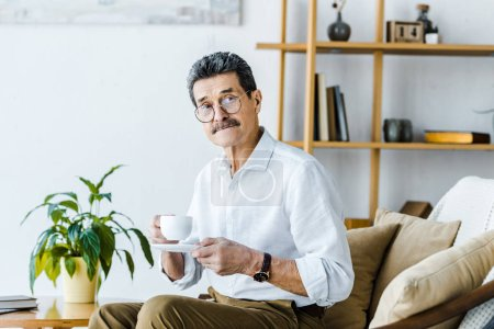 Photo for Senior man holding cup with coffee while sitting on sofa - Royalty Free Image
