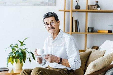 Photo pour Senior homme tenant la tasse à café assis sur le canapé - image libre de droit