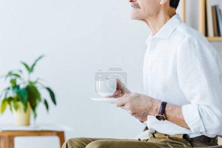Foto de Recortada la visión del jubilado hombre sosteniendo la taza con el café en casa - Imagen libre de derechos