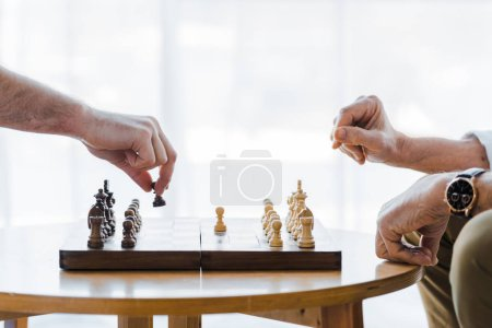 Photo for Cropped view of seniors playing chess at home - Royalty Free Image
