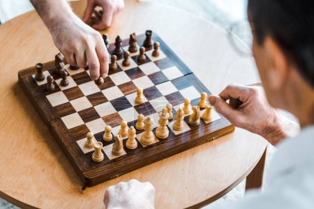 Photo for Selective focus of wooden chess board with retired men playing chess at home - Royalty Free Image