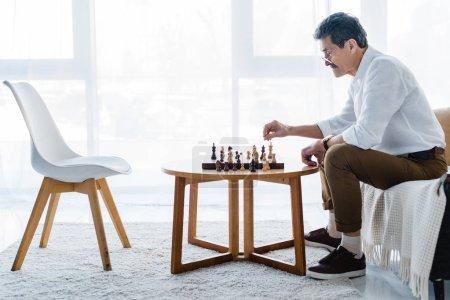 Photo pour Senior homme avec moustache jouant aux échecs à la maison - image libre de droit