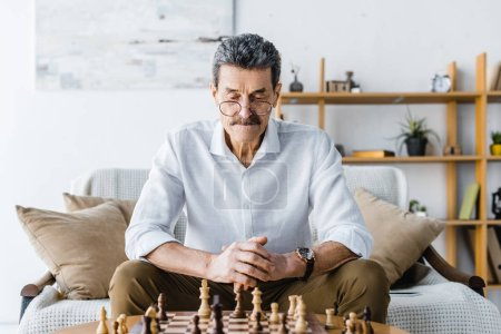 Photo for Pensive senior man with mustache looking at chess at home - Royalty Free Image