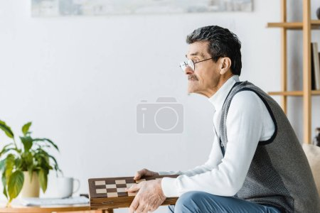 Photo for Thoughtful pensioner in glasses holding chess board in hands - Royalty Free Image